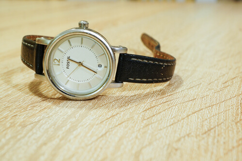 Fossil watch with leather belt on wooden background in soft focus