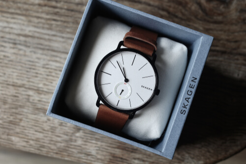 Modern Skagen contemporary watch on a vintage wooden table with box opened